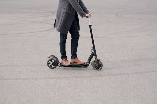 Low section of young contemporary businessman in coat, pants and boots standing on electric scooter while moving to work in the morning