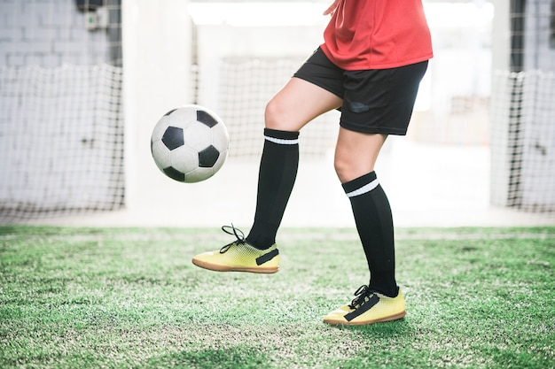 Low section of young female football player with soccer ball over foot training on green field at stadium