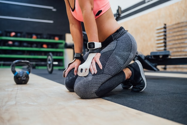 Low section young sportive woman exhausted indoor gym taking a break wearing smartwatch