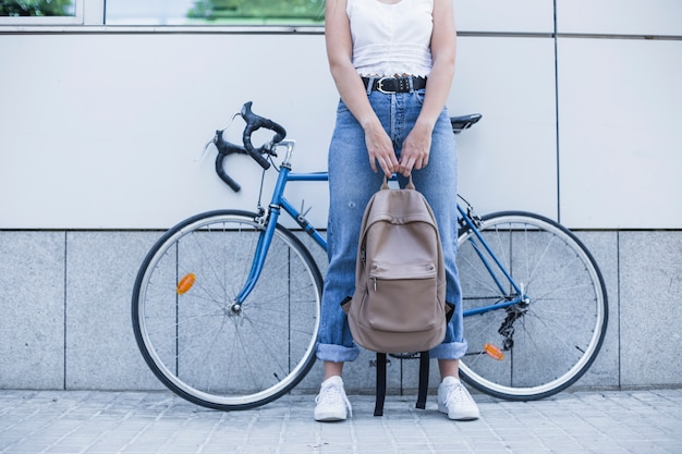 Low section of young woman holding backpack in her hand standing against bicycle