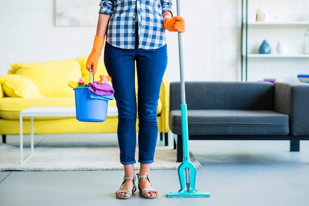 Low section of young woman holding bucket with cleaning supplies and mop