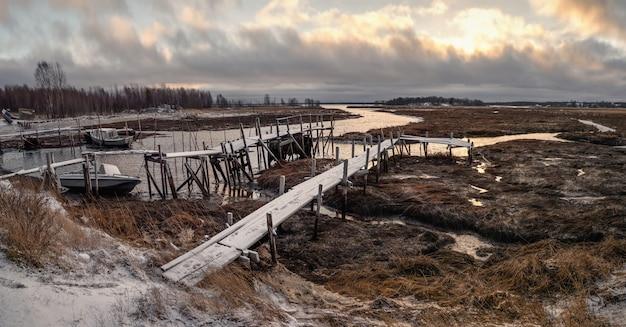 Отлив. рыбацкая пристань в аутентичной северной деревне умба. кольский полуостров, россия.
