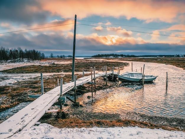 干潮。本格的な北部の村、ウンバにあるボート付きの釣り桟橋。コラ半島、ロシア。