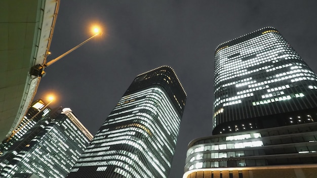 Low or uprisen angle view of modern skyscraper tower building in the night that represent futuristic