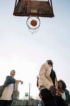 Low view group of friends playing basketball outdoors