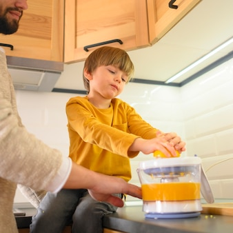 低ビューの子供とパパがオレンジジュースを作る