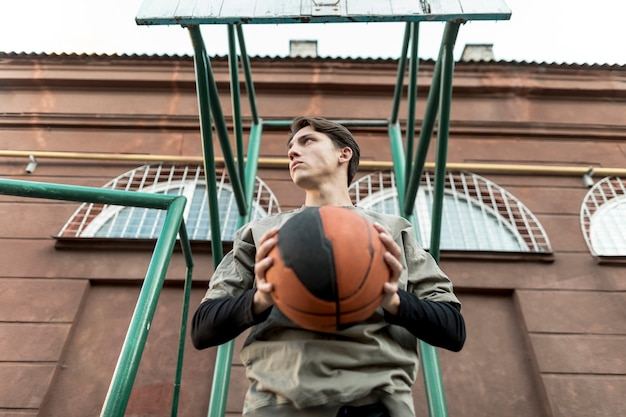 Low view man holding a basketball