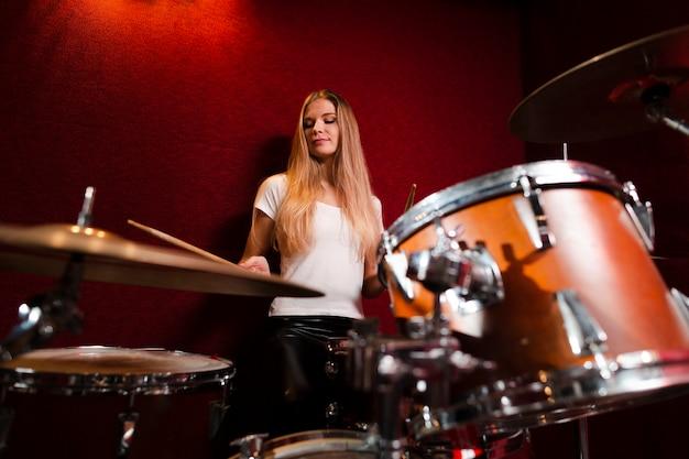 Низкий вид девушка играет на барабанах
