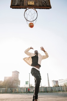 Low view teenager playing basketball outdoors