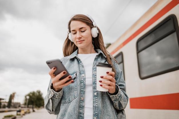 Женщина с низким видом слушает музыку на платформе поезда