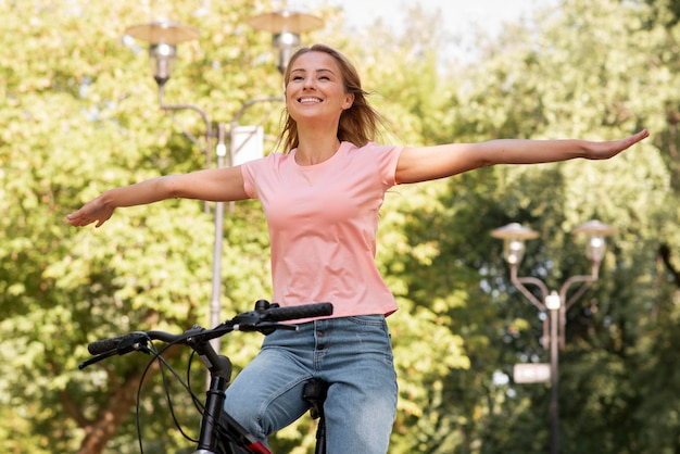 Low view woman riding without holding the bike with hands