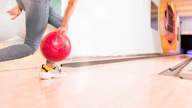 Low view woman throwing bowling ball