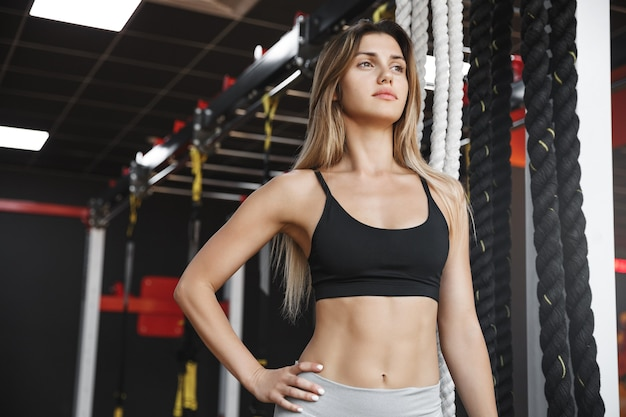 Lowe-angle shot assertive, strong and fit healthy female athlete with six-pack abdominal muscles, holds arm on waist.