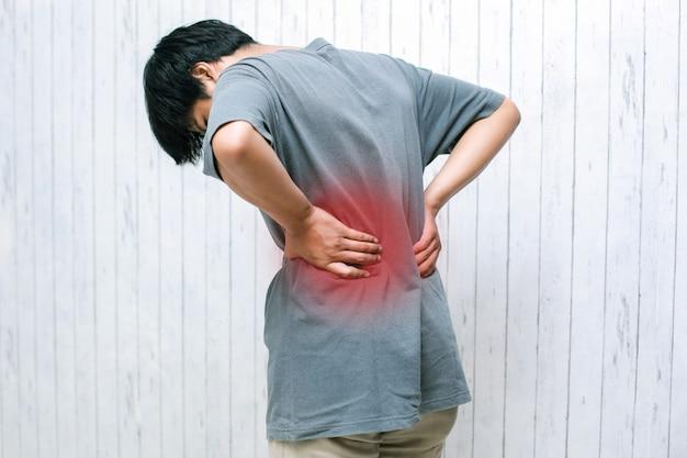 Боль в пояснице с молодым человеком, держащим спину от боли