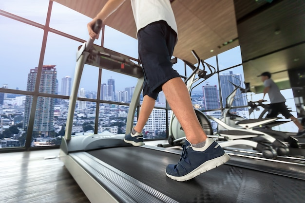 Lower body at legs part of young man in sportswear running on treadmill machine at fitness