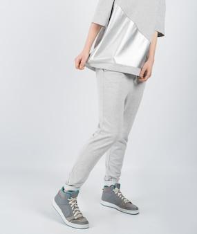 灰色の服とスニーカーを身に着けている若い美しい少女の下半身セクション