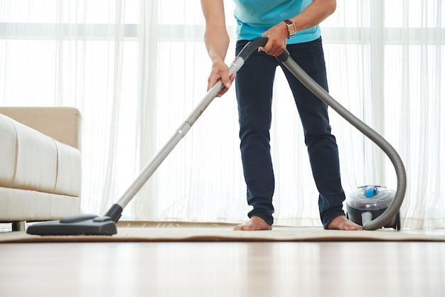Lower body shot of unrecognizable man vacuuming carpet at home