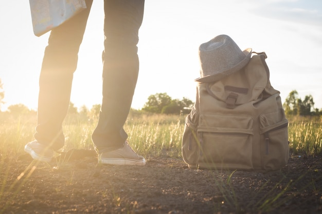 Lower part of asian men holding map standing and beside has vintage backpack with hat at countryside nature, lens flare of sunshine , travel concept
