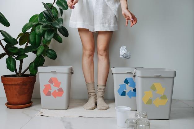 Нижняя часть женщины сортирует мусор, бросая дома в небольшую корзину для мусора кусок скомканной бумаги. их несколько, со стрелками разного цвета.
