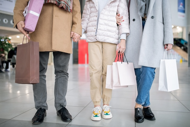 ショッピングの後、ショッピングモールで時間を過ごしながら買い物をする紙袋を3つ持っているカジュアルな家族の下部