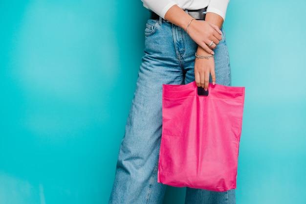 フクシアピンク繊維の買い物袋を保持しているブルージーンズの若いカジュアルな女性の買い物客の下部