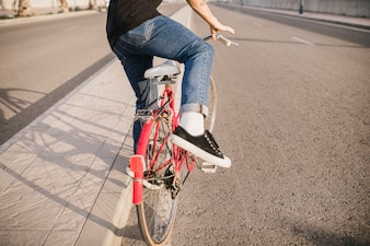 Lowsection of man sitting on red bicycle