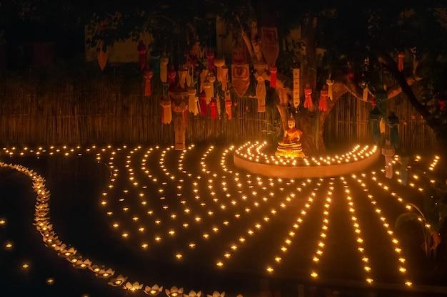 Loy krathong 축제, 불교 승려가 태국 치앙마이 판타오 사원에 있는 부처에게 촛불을 밝힙니다.