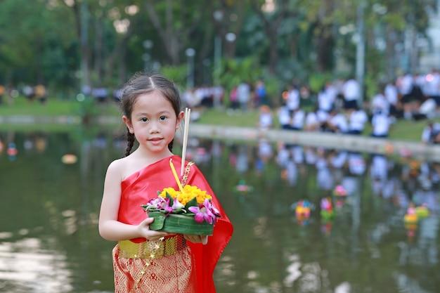 Loy krathong festival, child girl in thai dress holding krathong to celebrate festival in