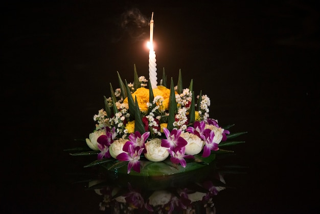 Loy krathong festival, people buy flowers and candle to light and float on water, thailand