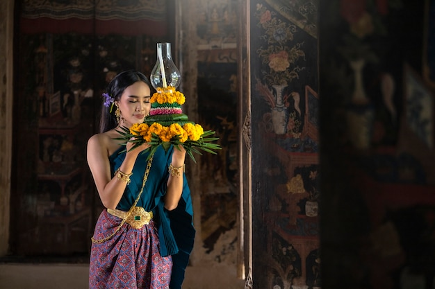 Loy krathong festival thailand. asian women are loy krathong for bless the buddha color gold.