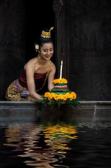 Фестиваль лой кратонг в таиланде. азиатские женщины лой кратонг на реке ночью.