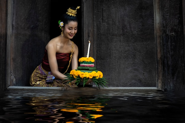 Loy krathong festival thailand. asian women are loy krathong on a the river at night.