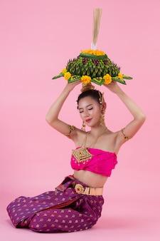 Фестиваль лой кратонг. женщина в традиционной тайской одежде держит украшенную плавучую