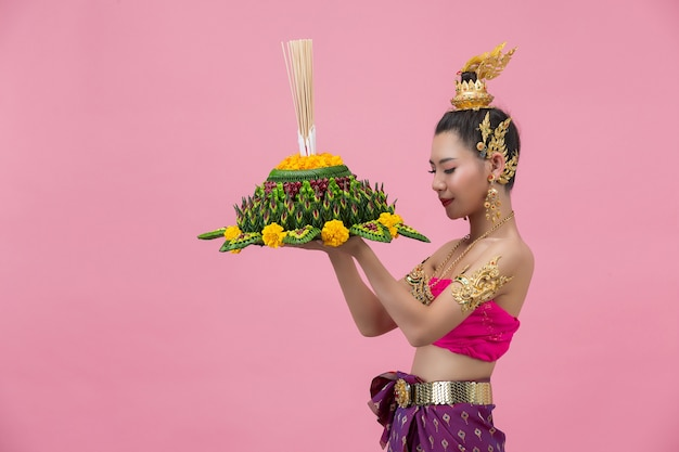 Loy krathong festival. woman in thai traditional outfit holding decorated buoyant