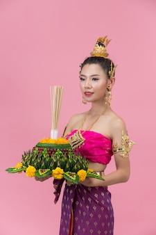 Loy krathong festival; donna in abito tradizionale tailandese con decorazioni galleggianti