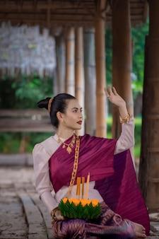 Loy krathong традиционный фестиваль thailand.asia женщина в тайском платье традиционного проведения кратонг.
