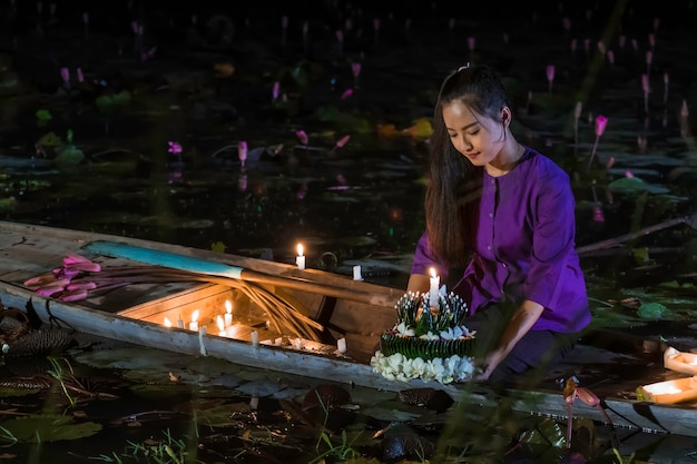 Loy kratong festival thailand. asian women are loy kratong on a boat in the lotus pond.