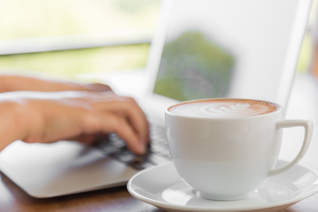 Lpersonは、次のコーヒーを飲んでラップトップに取り組んで