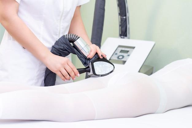 Lpg массаж тела девушки в спа. девушке делают аппаратный массаж, для массажа на ней специальный комбинезон.
