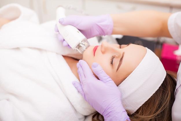 Женщина получает аппаратный массаж lpg в клинике красоты. профессиональный косметолог работает