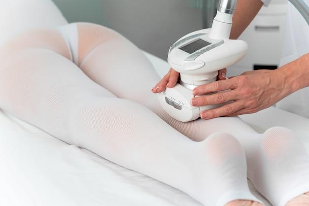 スパサロンで足のアンチセルライトマッサージを取得する特別な白いスーツの女性。 lpg、およびクリニックでの体の輪郭の治療。