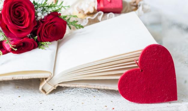 赤いバラとヴィンテージの空白の本とltoの愛の本を意味する心の詳細を感じた