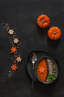 Ltraditional pumpkin homemade cream-soup with seeds crackers and little pumpkins.