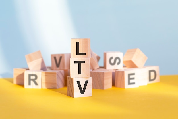 Ltv written on wooden cubes - arranged in a vertical pyramid, grey and yellow background, ltv - short for lifetime value, business concept