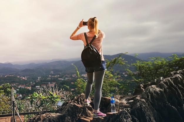 ラオス、ルアンパバーン-2018年6月29日-アジアの女性観光客が2018年6月29日にラオスのルアンパバーンのプーシー山の頂上で夕日の写真を撮ります