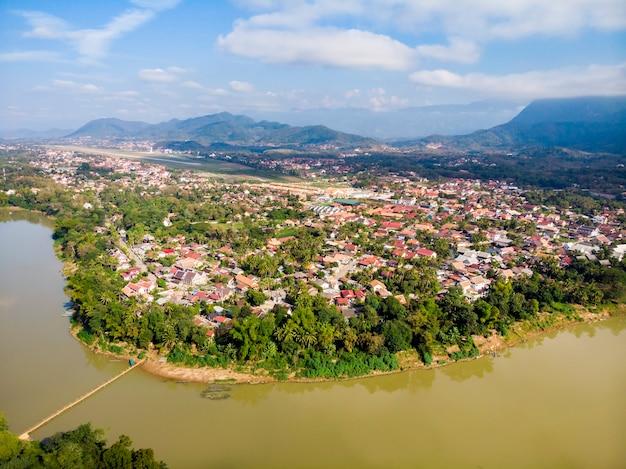 Луангпхабанг, лаос. вид с воздуха на город луангпхабанг в лаосе. облачное небо над маленьким городом, окруженным горами. автомобильное движение и река