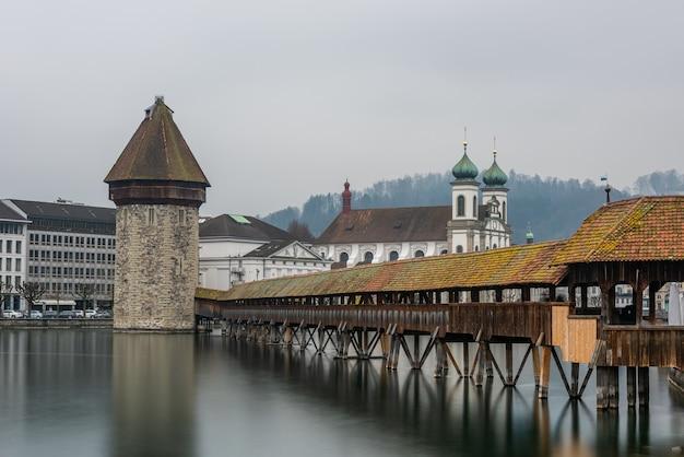 スイスのルツェルンの曇り空の下で水に囲まれたルツェルンイエズス会教会