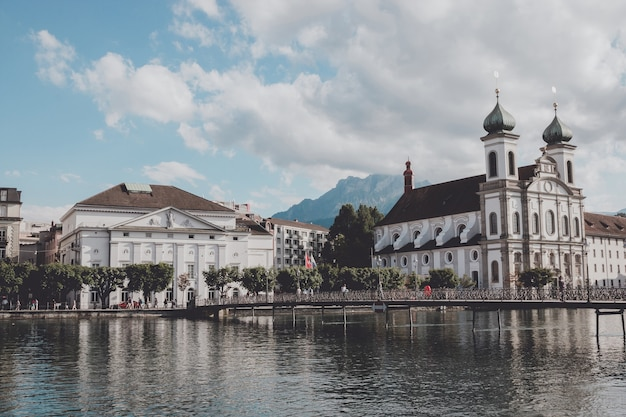 Lucerne, switzerland - july 3, 2017: panoramic view of lucerne city with jesuit church and river reuss. dramatic sky and sunny summer landscape
