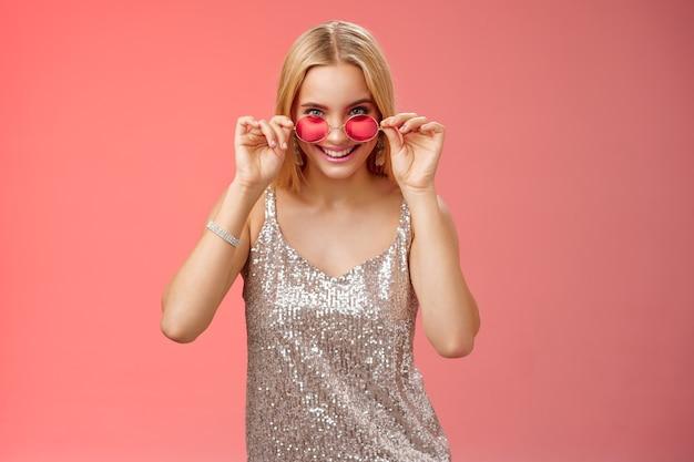 은빛으로 빛나는 드레스 선글라스를 끼고 친구들과 나이트클럽을 즐기는 운이 좋은 매력적인 세련된 유럽 금발 여성은 빨간색 배경에 서 있는 흥미롭고 흥미로운 엿보기 카메라를 보고 있습니다.