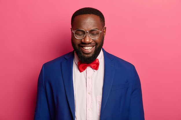 Lucky bearded male entrepreneur laughs gladfully, feels ecstatic and happy to hear about successful plan, meets with business partners